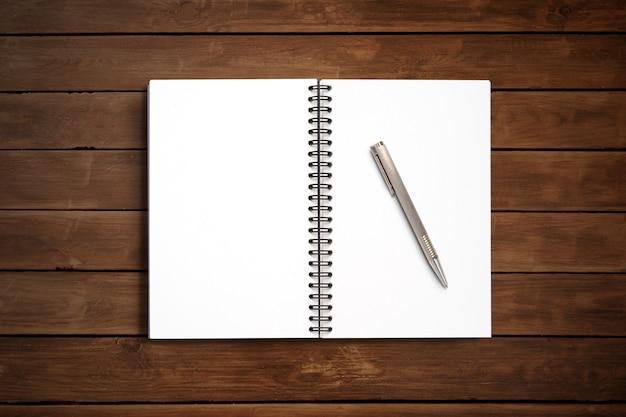 Vista superior design mínimo de notebook aberto com caneta em fundo de madeira.