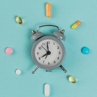 Vista superior despertador com remédio em cima da mesa