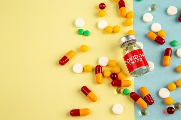 Vista superior diferentes comprimidos com vacina em fundo amarelo-azul