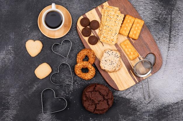 Vista superior diferentes cookies e xícara de café na superfície escura