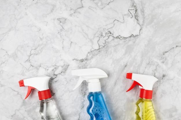 Vista superior diferentes frascos de spray na mesa de mármore