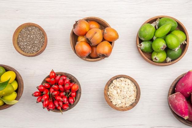 Vista superior diferentes frutas frescas dentro de pratos em fundo branco maduro exótico vida saudável cor tropical