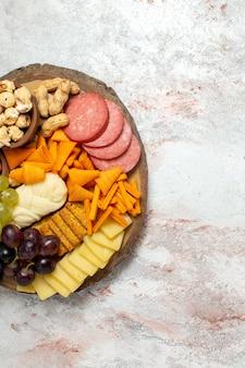 Vista superior diferentes lanches nozes cips uvas queijo e salsichas na superfície branca nozes lanche refeição alimentos frutas