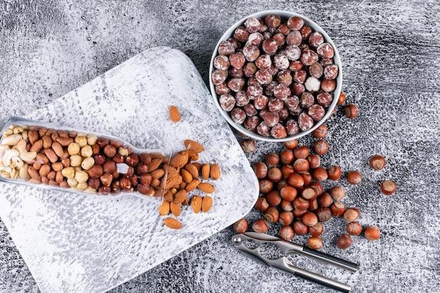 Vista superior diferentes nozes em garrafa cheia de nozes e tigela com quebra nozes e nozes, pistache, amêndoa, amendoim, caju, pinhões