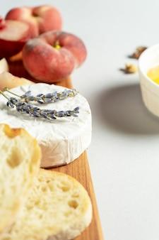 Vista superior diferentes tipos de queijos na tábua de madeira. queijo com figo, pêssego, mel, ciabatta e nozes, copo de vinho tinto. comida elegante plana leigos em fundo cinza. copie o espaço. foco suave