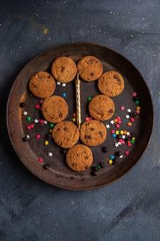 Vista superior distante biscoitos de chocolate deliciosos dentro de um prato redondo escuro no fundo escuro biscoito biscoito chá doce