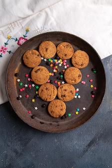 Vista superior distante biscoitos de chocolate deliciosos dentro de uma placa redonda marrom no fundo branco biscoito doce chá