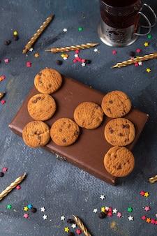 Vista superior distante biscoitos de chocolate saborosos na caixa marrom com chá e velas no fundo cinza escuro.