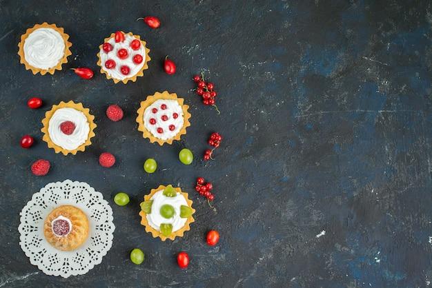 Vista superior distante bolinhos deliciosos com creme e frutas frescas na mesa de frutas escura
