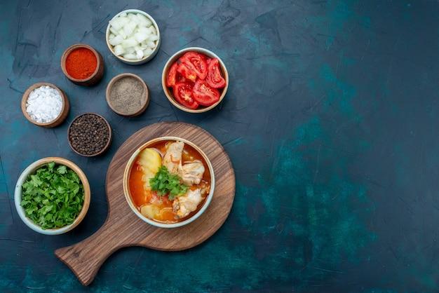 Vista superior distante canja de galinha com batatas junto com sal pimenta legumes frescos na mesa azul-escura sopa carne comida jantar refeição