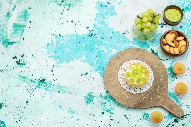 Vista superior distante de um pequeno bolo com creme delicioso e biscoitos de uvas verdes frescas e fatiados isolados na mesa de luz azul, bolo de frutas doces