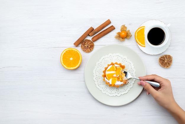 Vista superior distante de um pequeno bolo com creme e laranjas fatiadas junto com café e canela na mesa leve, bolo de frutas, biscoito doce, açúcar