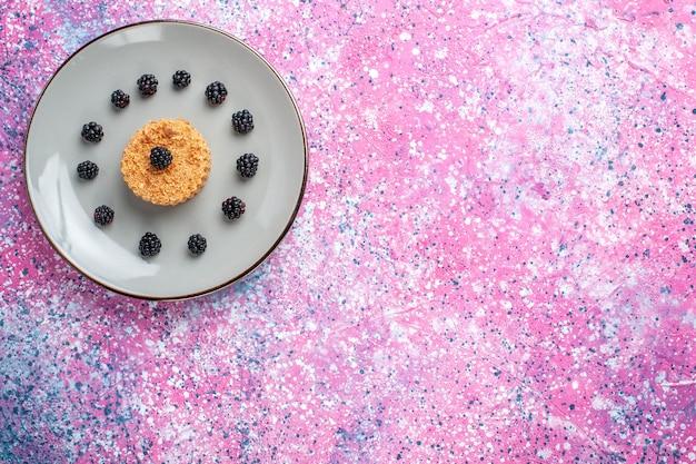 Vista superior distante de um pequeno bolo com frutas na superfície rosa