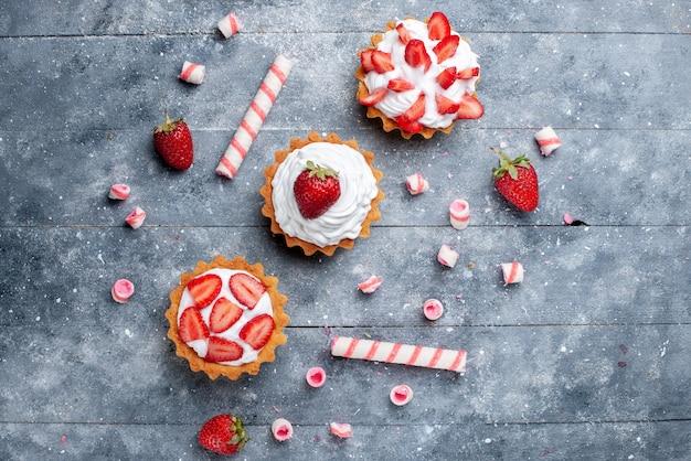 Vista superior distante de um pequeno bolo cremoso com morangos fatiados e frescos, juntamente com doces em barra cinza, bolo de frutas vermelhas