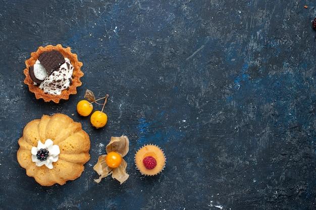 Vista superior distante de um pequeno bolo delicioso junto com um biscoito no escuro, bolo de biscoito doce de frutas assado