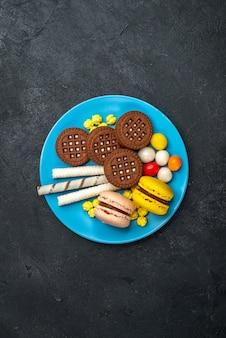 Vista superior distante deliciosos macarons franceses com doces e biscoitos de chocolate em uma superfície cinza escuro biscoito bolo de açúcar doce assar biscoito