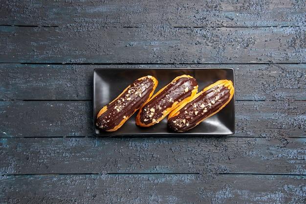 Vista superior distante éclairs de chocolate em placa retangular em fundo escuro de madeira