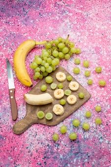 Vista superior distante frutas frescas fatiadas, uvas e bananas na superfície roxa Foto gratuita
