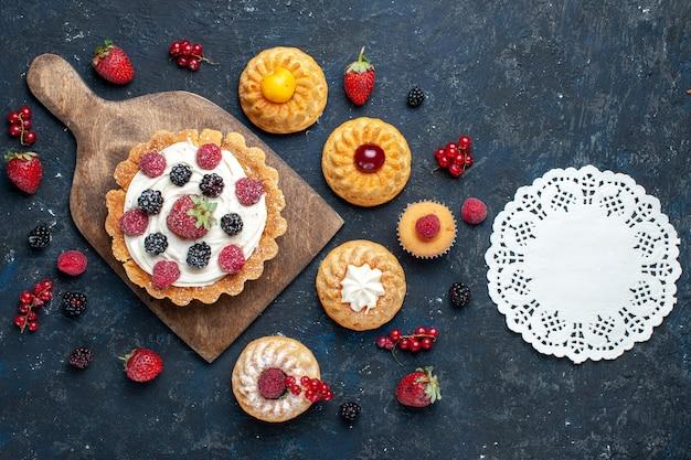 Vista superior distante, um bolo gostoso com creme e frutas vermelhas junto com biscoitos de pulseira em um biscoito de bolo de frutas silvestres escuro