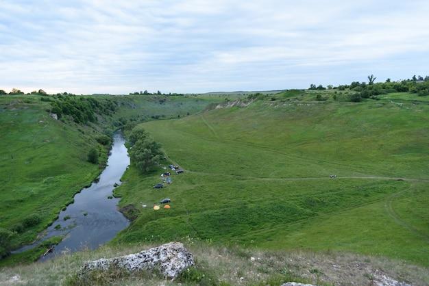 Vista superior do acampamento perto de um pequeno rio com carros e tendas, conceito de turismo