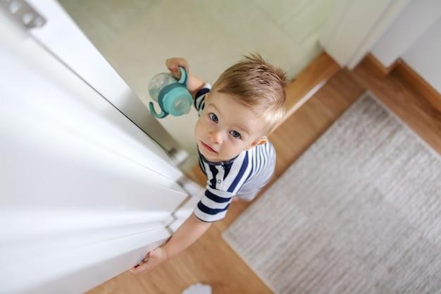 Vista superior do adorável garotinho loiro com lindos olhos azuis, segurando sua garrafa com água e olhando para a câmera.