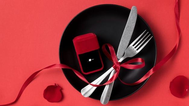 Vista superior do anel de noivado do dia dos namorados no prato com talheres e fita
