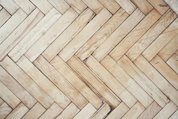 Vista superior do antigo piso de parquet de madeira escovado e desgastado feito de muitos suportes em padrão espinha