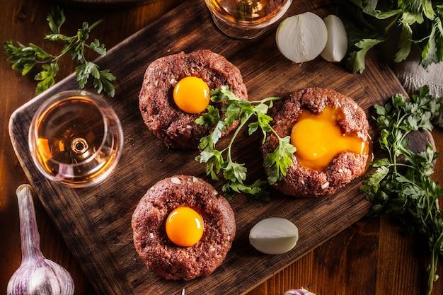 Vista superior do apetitoso bife tártaro com deliciosa gema de ovo e álcool. servido sobre uma mesa de madeira com cebola e ervas.