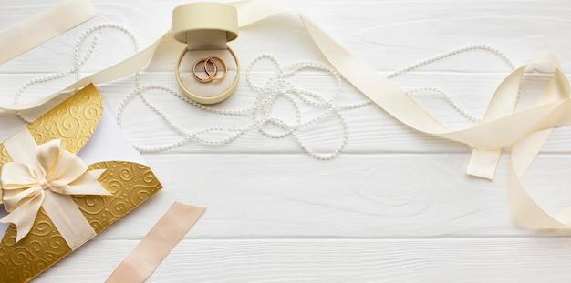 Vista superior do arranjo de pérolas e anéis de casamento