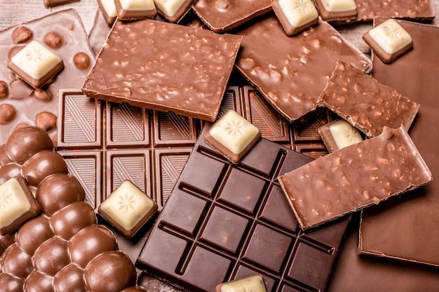 Vista superior do arranjo de vários tipos de chocolate. deliciosa mistura de chocolate. vista superior de pedaços de barra de chocolate com chips. barra com pedaços espalhados