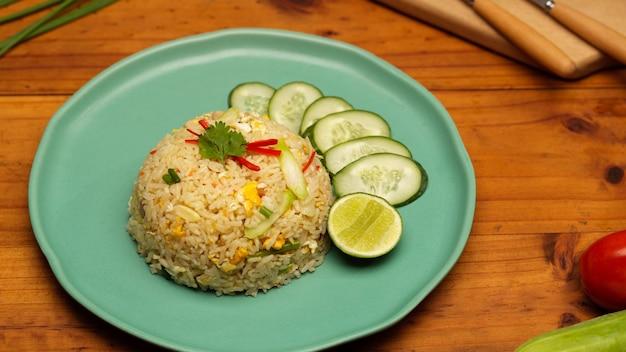 Vista superior do arroz caseiro frito tailandês com fatias de pepino e limão na mesa de madeira