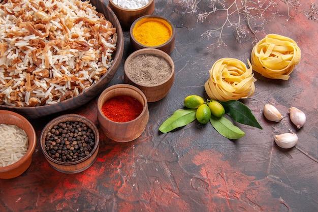 Vista superior do arroz cozido com temperos na superfície escura da foto do prato de refeição escuro