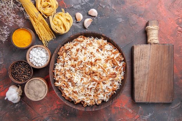 Vista superior do arroz cozido junto com os temperos em uma mesa escura com pratos de comida