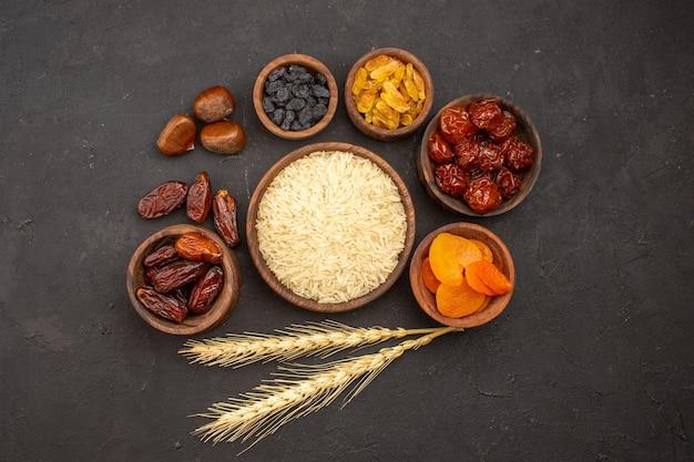 Vista superior do arroz cru com diferentes passas na superfície cinza Foto gratuita
