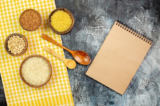 Vista superior do arroz cru com feijão e aletria dentro de pequenas panelas na mesa cinza claro