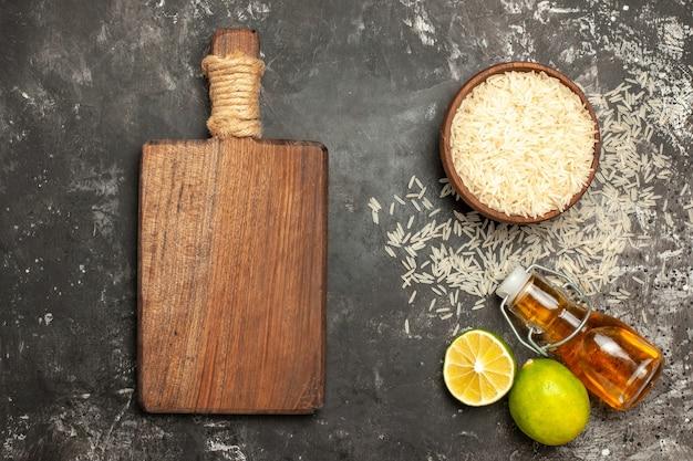 Vista superior do arroz cru com limão e óleo em óleo alimentar cru de superfície escura