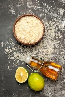 Vista superior do arroz cru com limão e óleo na superfície escura com cor de fruta crua