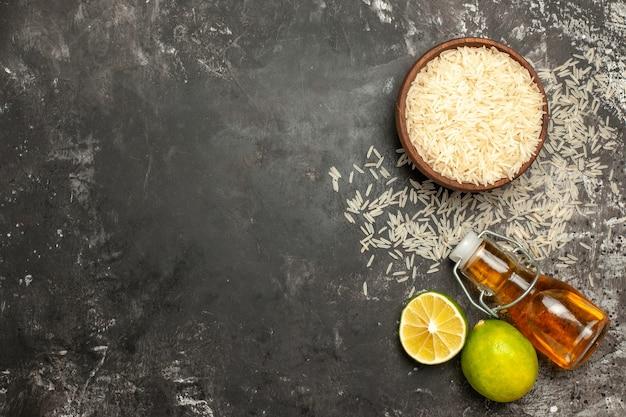 Vista superior do arroz cru com limão e óleo no chão escuro com alimentos crus cor de frutas