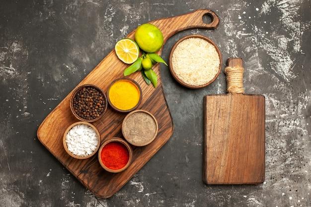 Vista superior do arroz cru com limões e temperos em uma superfície escura com especiarias para alimentos crus