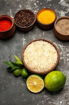 Vista superior do arroz cru com limões e temperos na superfície escura de alimentos crus, cor de frutas