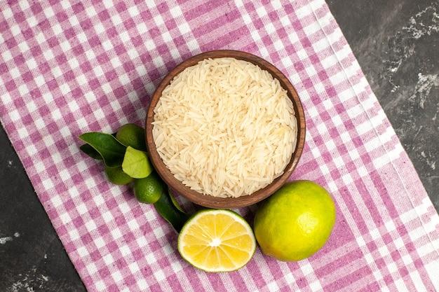 Vista superior do arroz cru com limões na superfície escura de alimentos crus, cor de frutas