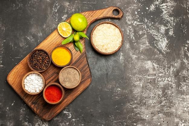 Vista superior do arroz cru com temperos e limões em uma superfície escura com especiarias alimentares