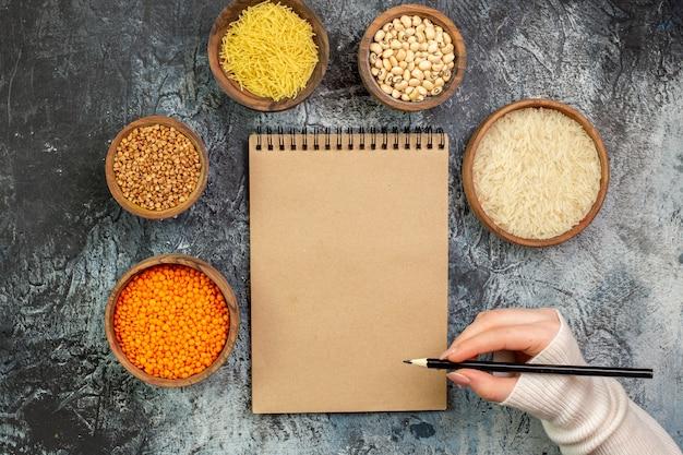 Vista superior do arroz cru com vermicelli e trigo sarraceno cru dentro de pequenos potes na mesa cinza claro