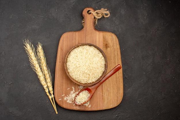 Vista superior do arroz cru dentro de uma placa de madeira marrom em uma superfície cinza escura