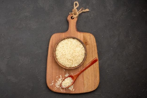 Vista superior do arroz cru dentro de uma placa de madeira marrom na superfície cinza