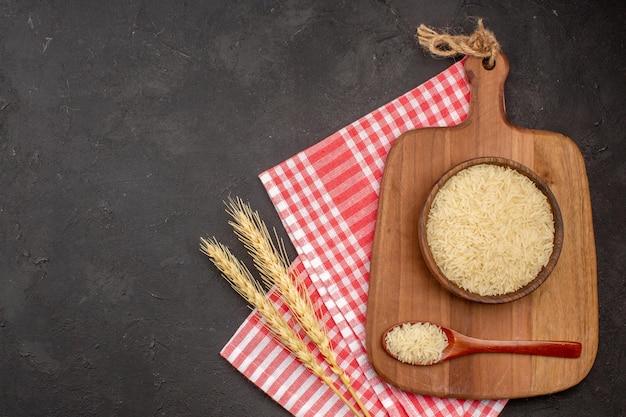 Vista superior do arroz cru dentro de uma placa de madeira na superfície cinza