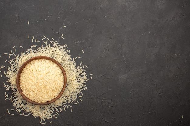 Vista superior do arroz cru dentro do prato em uma superfície cinza escura