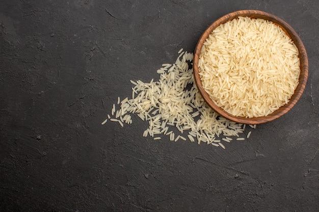 Vista superior do arroz cru dentro do prato marrom na superfície cinza escuro