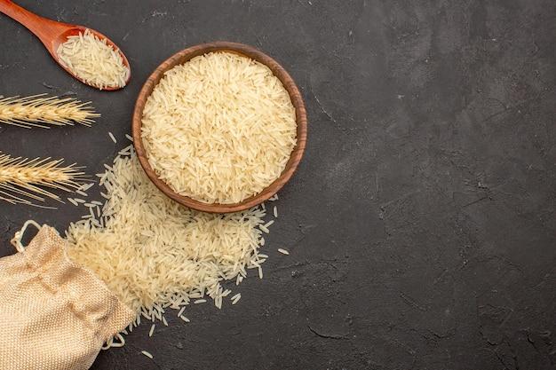Vista superior do arroz cru dentro do prato marrom na superfície cinza