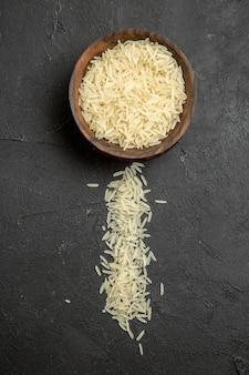 Vista superior do arroz cru dentro do prato marrom na superfície escura refeição arroz cru